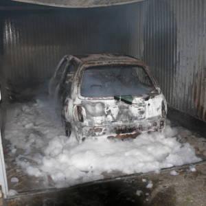 Feuerwehr löscht brennendes Auto in Garage
